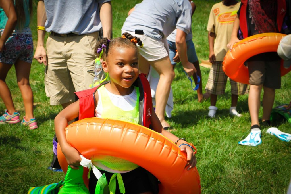 Girl with inner tube playing summer games