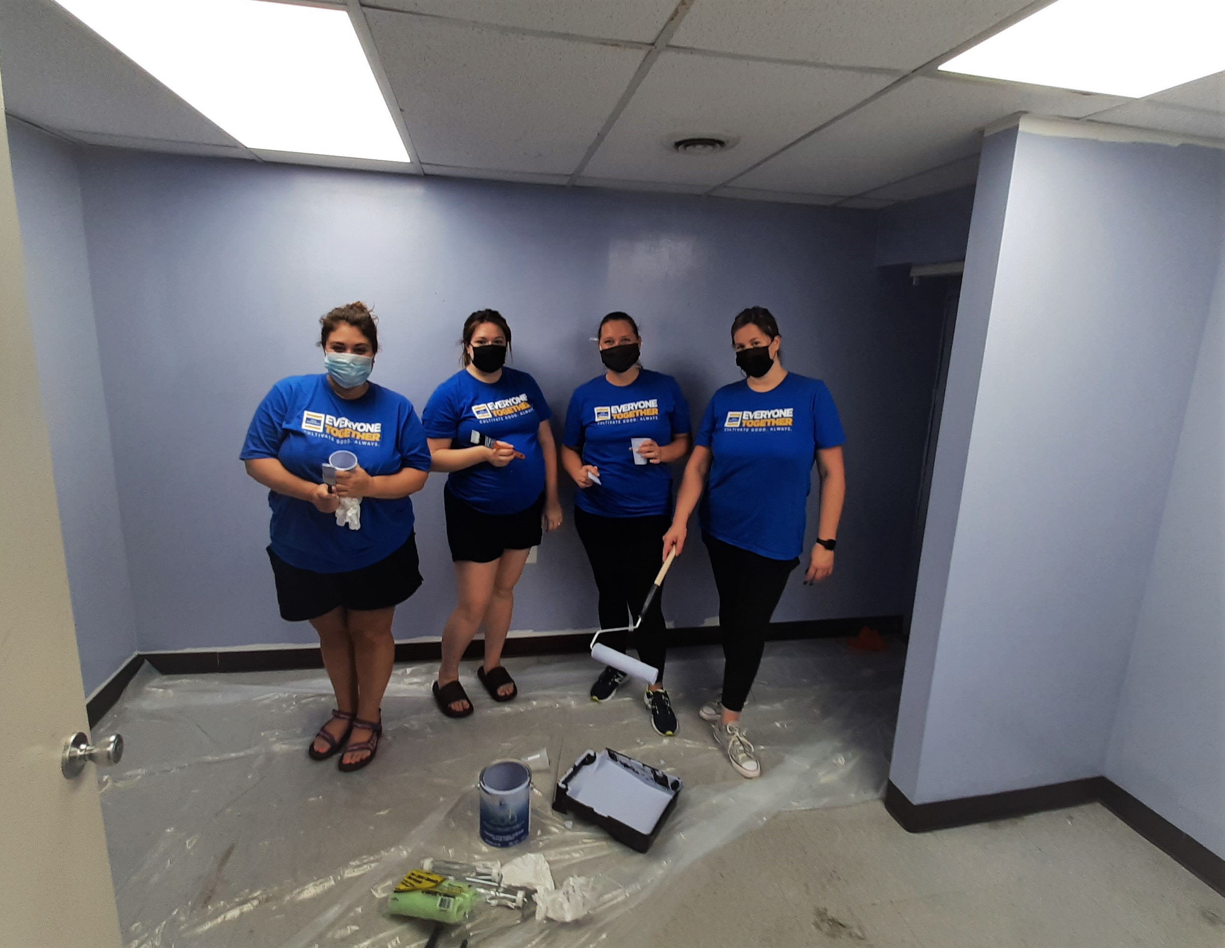 Four Old National Bank volunteers in blue shirts and paint rollers.