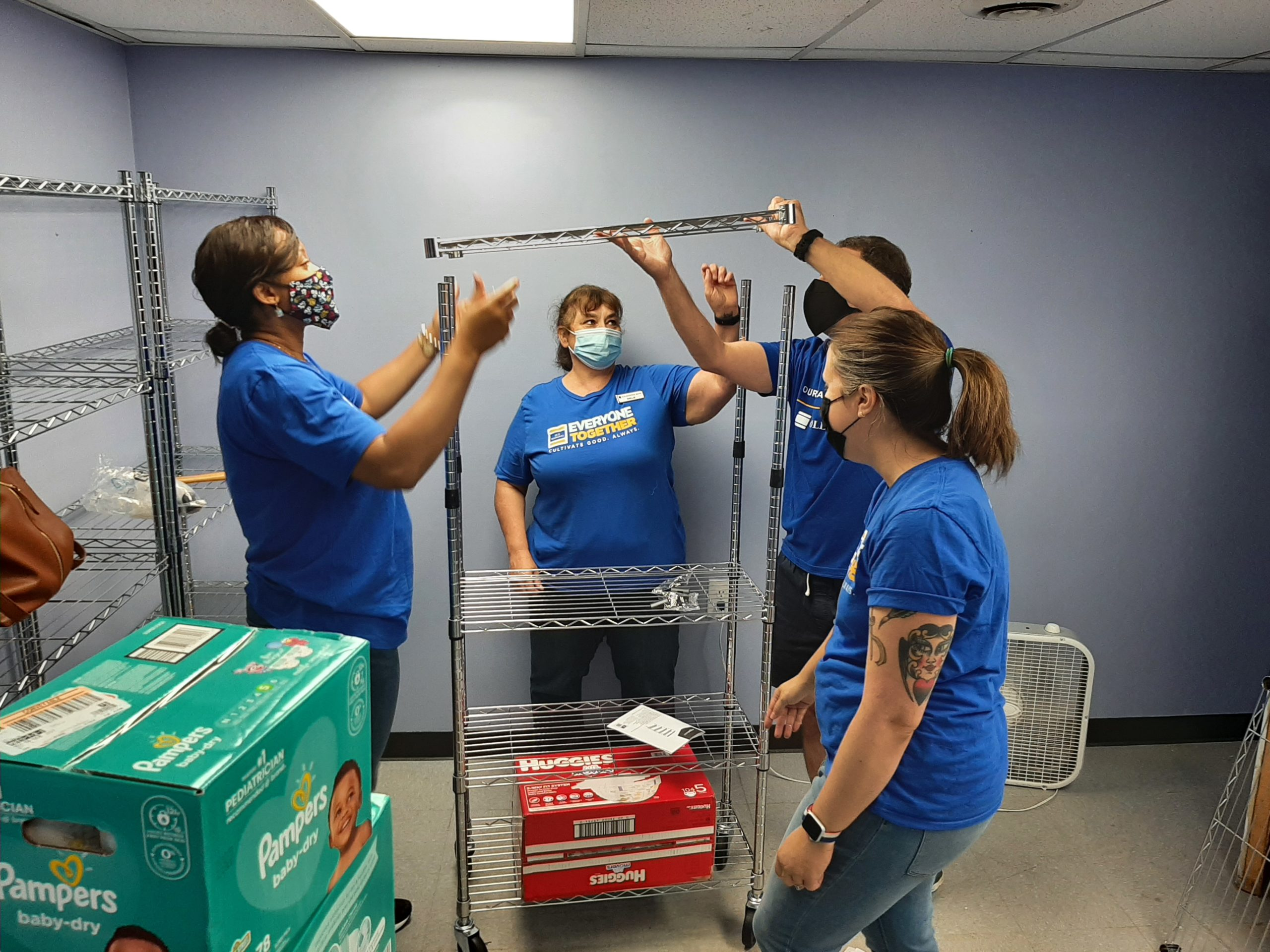 Four volunteers putting together shelving