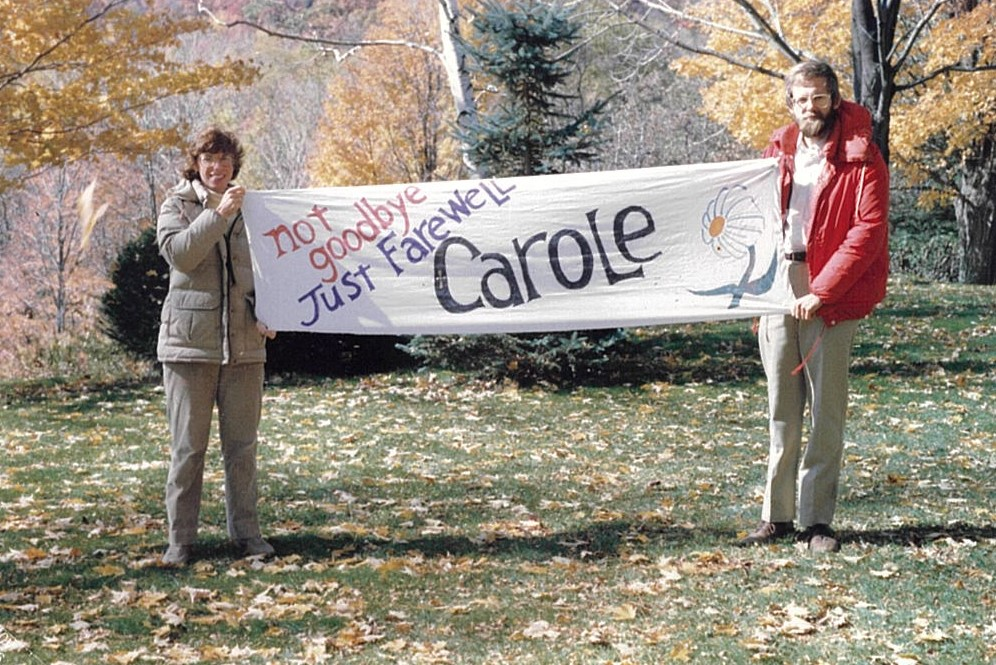 """Carole with goodbye banner that says """"Not Goodbye, Just Farewell"""""""