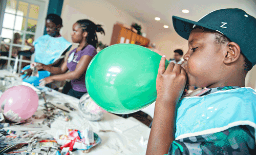kid blowing up a balloon