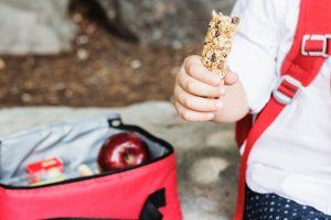 child with granola bar and lunch box